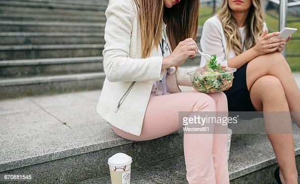 Two women having lunch break outdoors