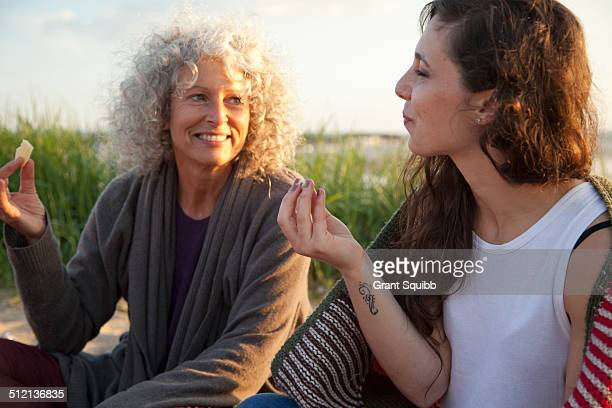 Two women having picnic on Bournemouth beach, Dorset, UK