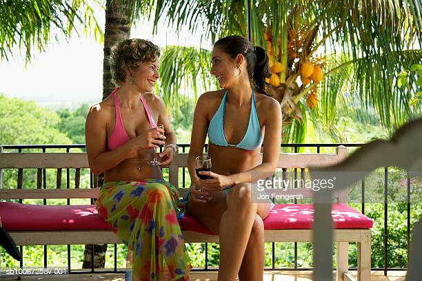 Two women having red wine at balcony