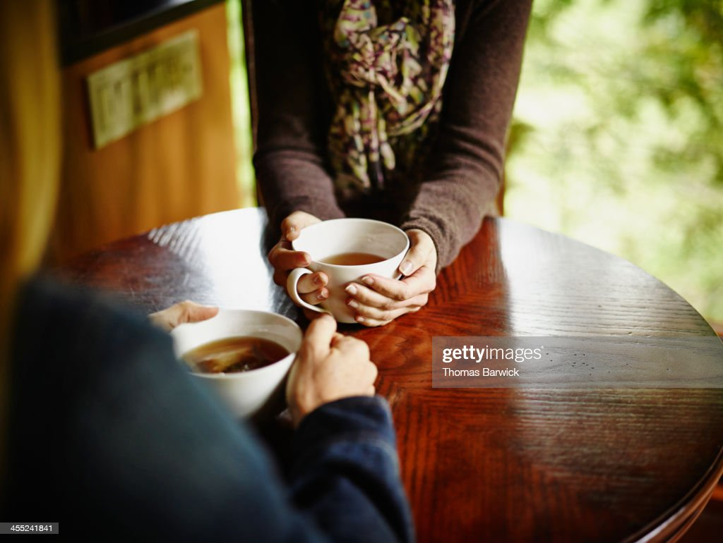 Two women having tea at table in cabin : Stock Photo