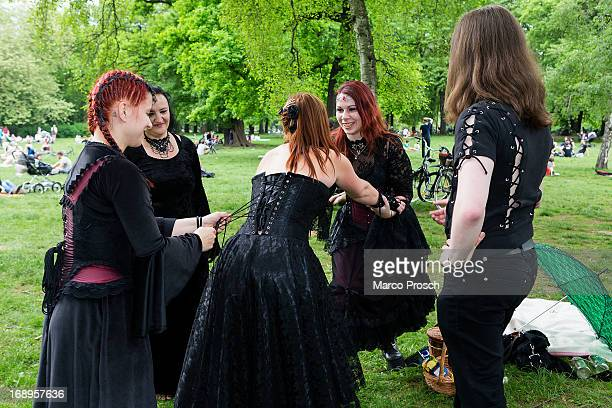Two women help their friend straightening her corset during the traditional park picnic on the first day of the annual WaveGotik Treffen or Wave and...
