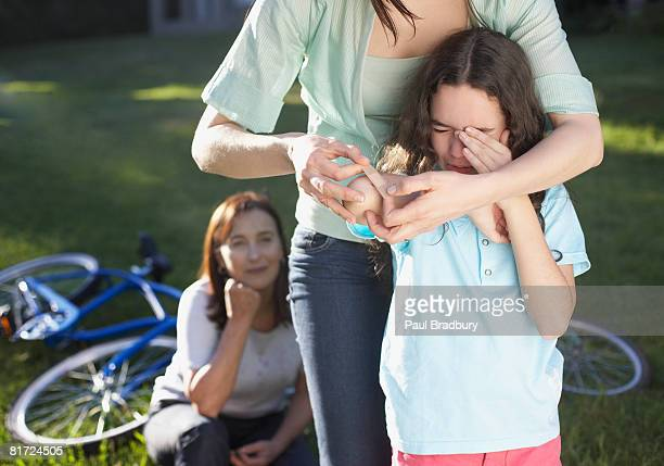 Two women helping an injured young girl who fell off her bike