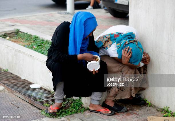 Two women hide their faces as Ethiopian domestic workers who were dismissed by their employers gather with their belongings outside their countrys...