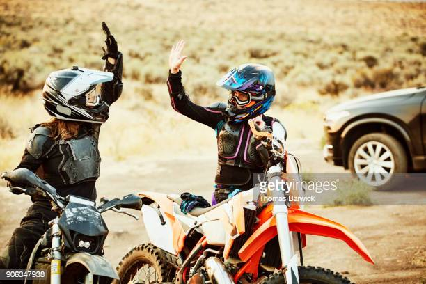 Two women high fiving after dirt bike ride in desert