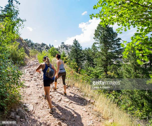 two women hiking up a mountain trail. - state park stock pictures, royalty-free photos & images