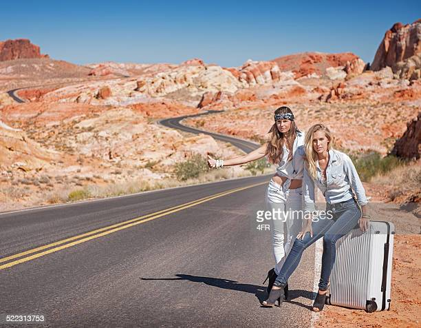 two women hitchhiking in the desert - valley of fire state park stock photos and pictures