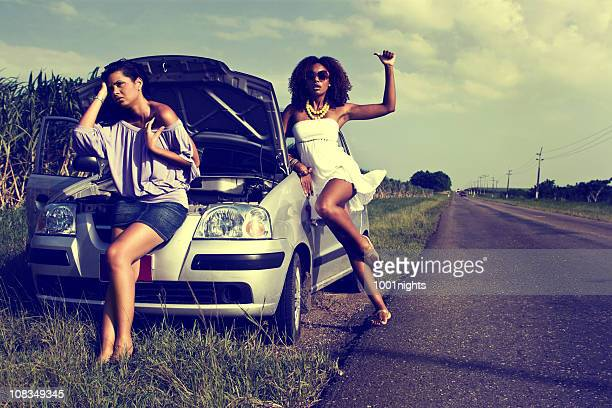 two women hitchhiking - short skirts in cars stock photos and pictures