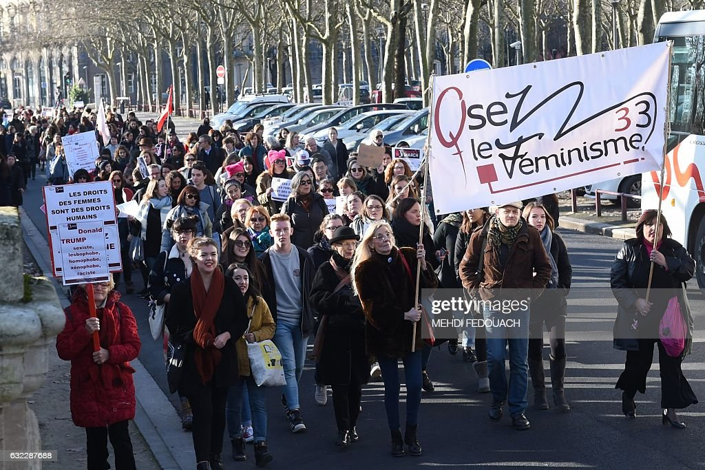 Two women hold a banner of the association Osez le feminisme (Dare Feminism) during a rally in solidarity with the Women's March taking place in Washington and many other cities on January 21, 2017 in Bordeaux, Southwestern France, one day after the inauguration of the US President. Protest rallies were held in over 30 countries around the world in solidarity with the Washington Women's March in defense of press freedom, women's and human rights following the official inauguration of Donald J Trump as the 45th President of the United States of America. / AFP / MEHDI