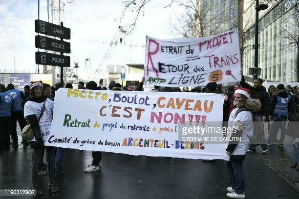 Two women hold a banner on December 24 2019 outside French train operator SNCF headquarters in SaintDenis near Paris during a demonstration on the...