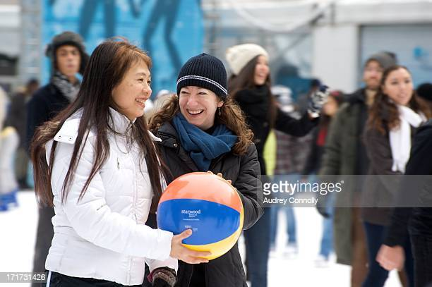 CONTENT] two women hold a beach ball during an event on the skating rink at Bryant Park Midtown Manhattan New York City
