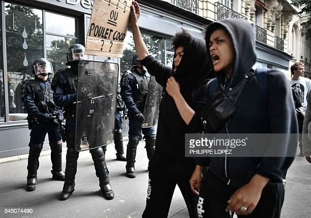 TOPSHOT Two women hold a placard and shout slogans as French CRS antiriot police stand guard during a demonstration against proposed government...