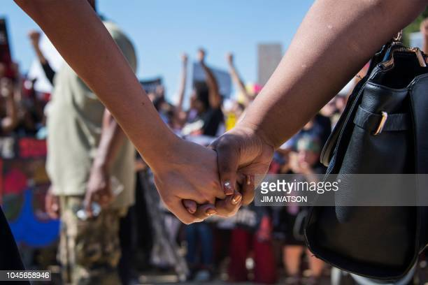 Two women hold hands as demonstrators protest US Supreme Court nominee Brett Kavanaugh near the US Capitol on October 4 in Washington DC Top...