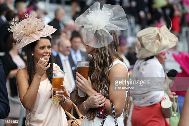 Two women hold pints of lager on ladies day on June 16, 2011 in Ascot, England. The five-day meeting is one of the highlights of the horse racing...