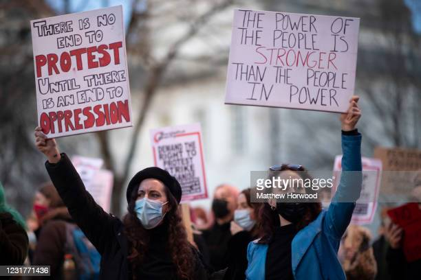 Two women hold signs during a protest outside Cardiff Central Police Station on March 17, 2021 in Cardiff, Wales. Legislation giving police greater...