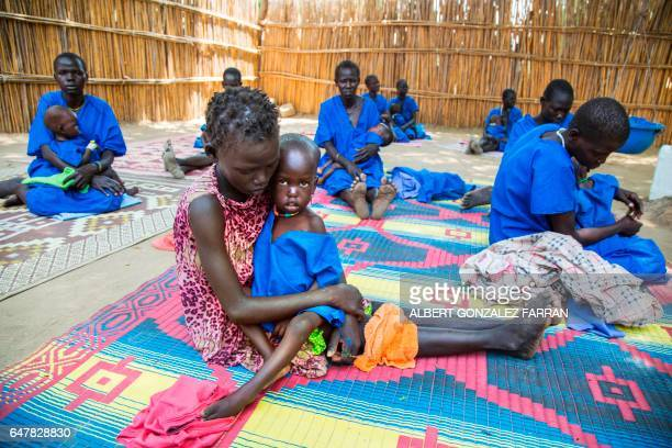 Two women hold their acute malnourished children on March 4 in a stabilisation centre in Ganyiel, Panyijiar county, in South Sudan. South Sudan was...