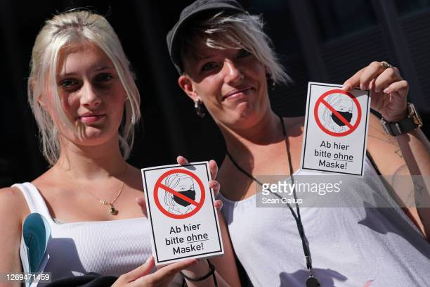 Two women hold up stickers that read From here on please without a mask as they march with coronavirus skeptics rightwing extremists and others in...