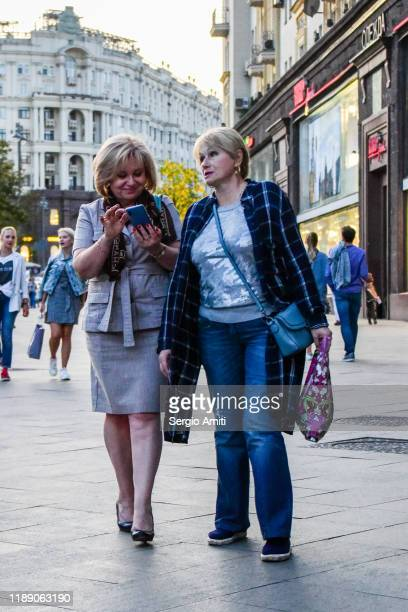 two women holding bags and using their phone while walking near red square in moscow, russia - sergio amiti stock pictures, royalty-free photos & images