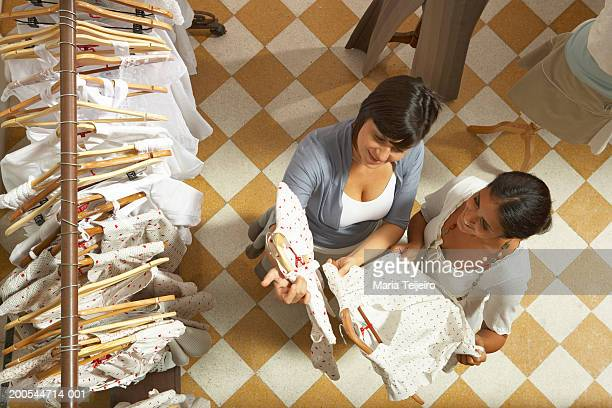two women holding dresses in shop, elevated view - looking down her blouse stock photos and pictures