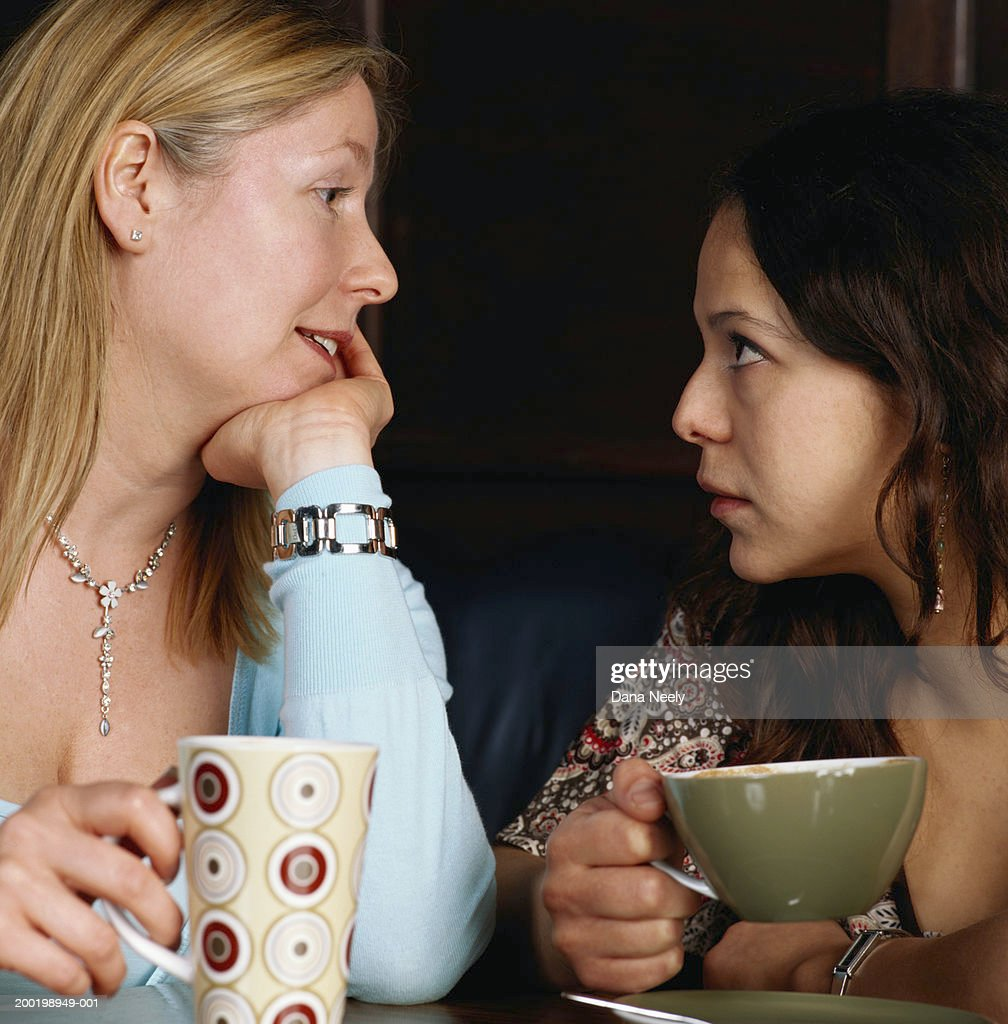 Two women holding drinks, looking at each other, close-up : Stock Photo