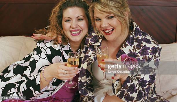 Two women holding glasses of champagne, smiling, portrait