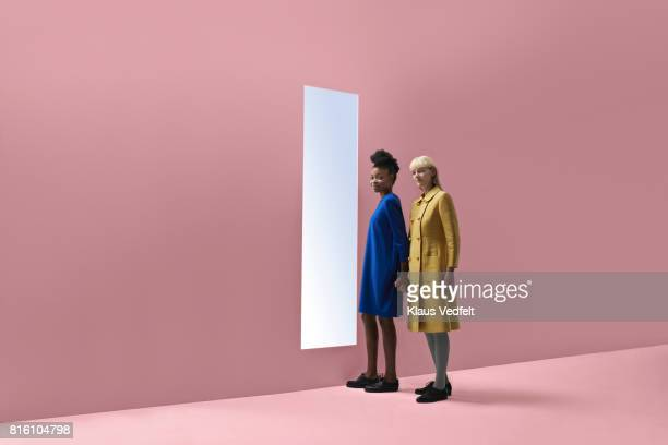 two women holding hands, standing in front of rectangular opening in coloured wall - fringe dress stock pictures, royalty-free photos & images