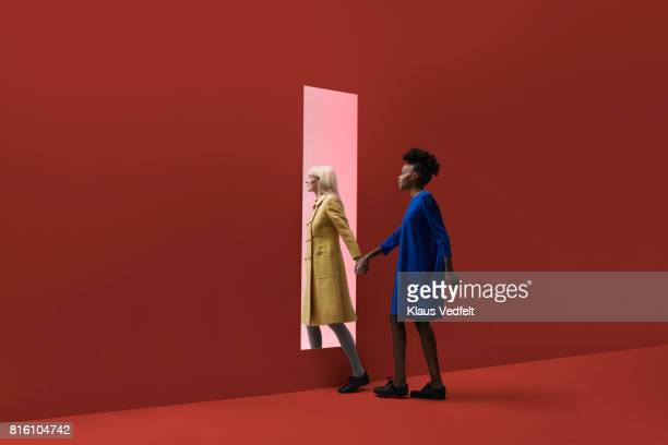 Two women holding hands, walking threw rectangular opening in coloured wall