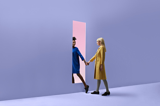 Two women holding hands, walking threw rectangular opening in coloured wall - gettyimageskorea