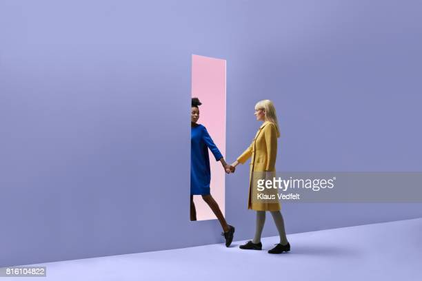 two women holding hands, walking threw rectangular opening in coloured wall - vestido azul fotografías e imágenes de stock