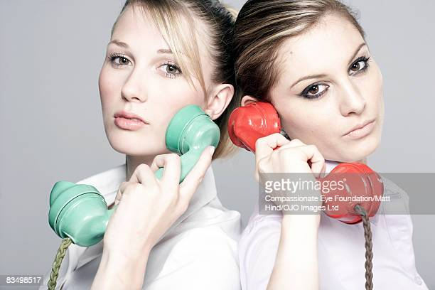 Two women holding phones, looking stern