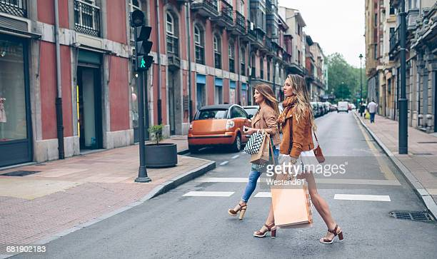 two women holding shopping bags crossing the street in the city - 背景に人 ストックフォトと画像