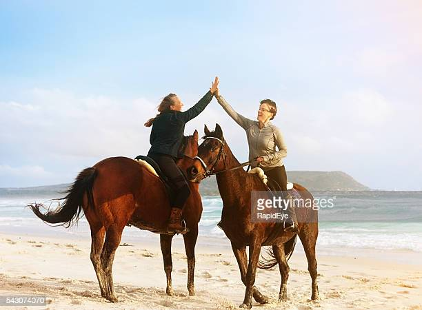 Two women horse riders greet each other on idyllic beach