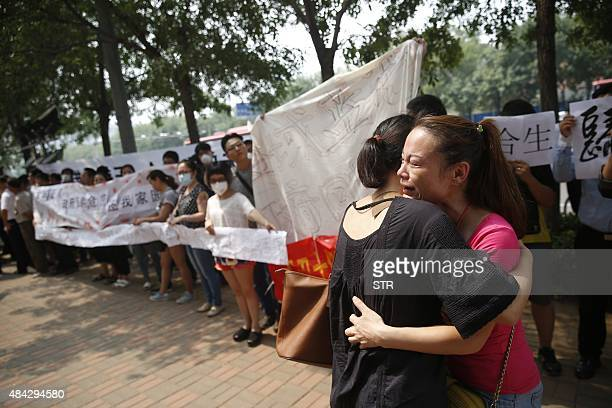Two women hug one another as they join other residents whose homes were destroyed in the explosion at a chemical warehouse last week in protest...