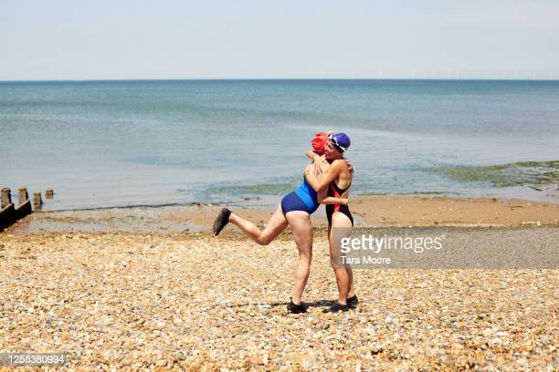two women hugging at seadside - horizon over water stock pictures, royalty-free photos & images