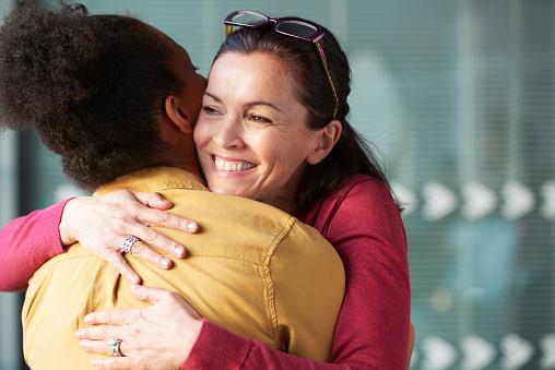 two women hugging at work - gettyimageskorea