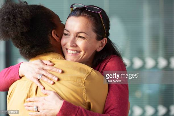 two women hugging at work - embracing stock pictures, royalty-free photos & images