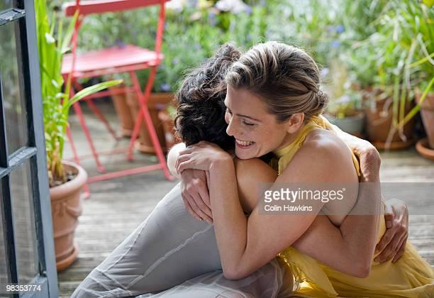 two women hugging on balcony - alleen mid volwassen vrouwen stockfoto's en -beelden