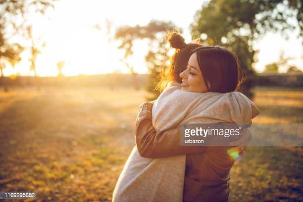 two women hugging - embracing stock pictures, royalty-free photos & images