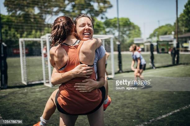 zwei frauen umarmen sich auf demfußball - frauenfußball stock-fotos und bilder