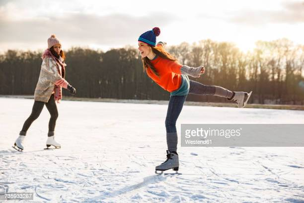 Two women ice skating on frozen lake