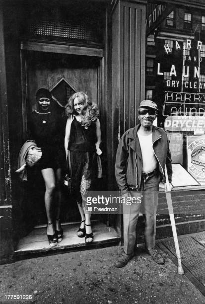 Two women in a doorway and a homeless man pose for a photograph New York City circa 1978