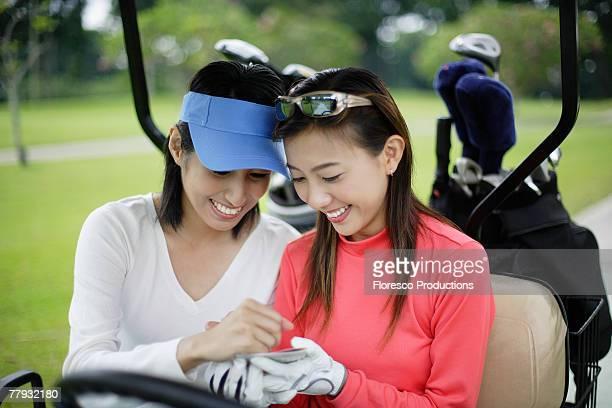 Two women in a golf cart