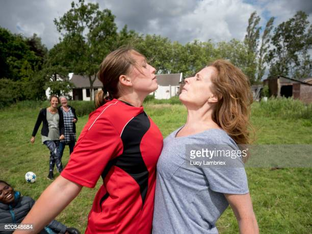 Two women in a physical confrontation during a recreational soccer game