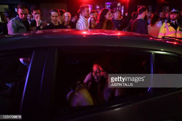 Two women in a taxi look at a mobile phone as they leave a street filled with revellers in the Soho area of London on July 4 after the police...