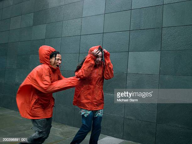 two women in anoraks struggling to walk against rainstorm, eyes closed - gale stock photos and pictures