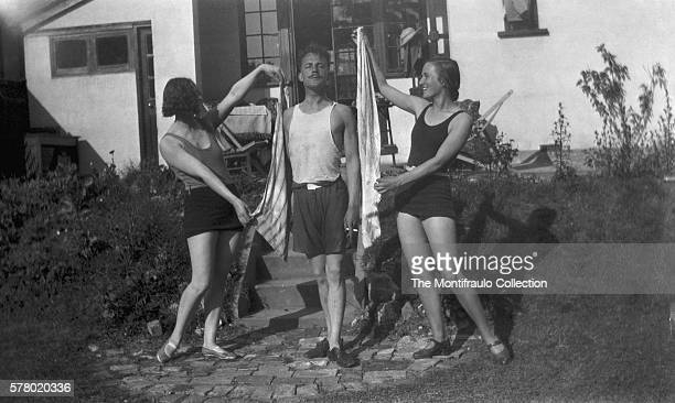 Two women in bathing costumes holding towels up as pretend drapes in front of a man in full regal pose in the back garden of house England circa 1930