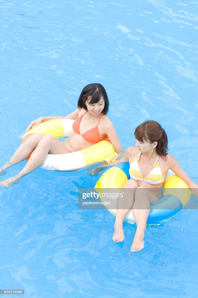 Two Women In Bathing Suits Floating In Inner Tubes Stock Photo ...
