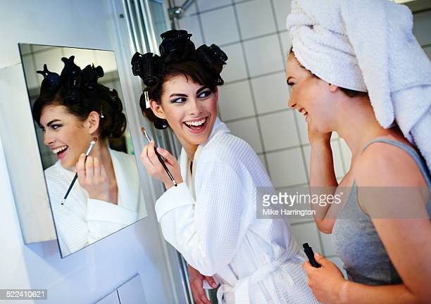 Two women in bathroom preparing for night out.