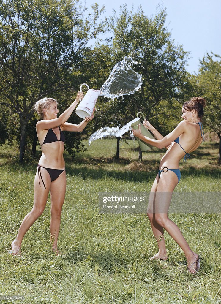 Two Women in Bikini Throwing Water at Each Other : Stock Photo