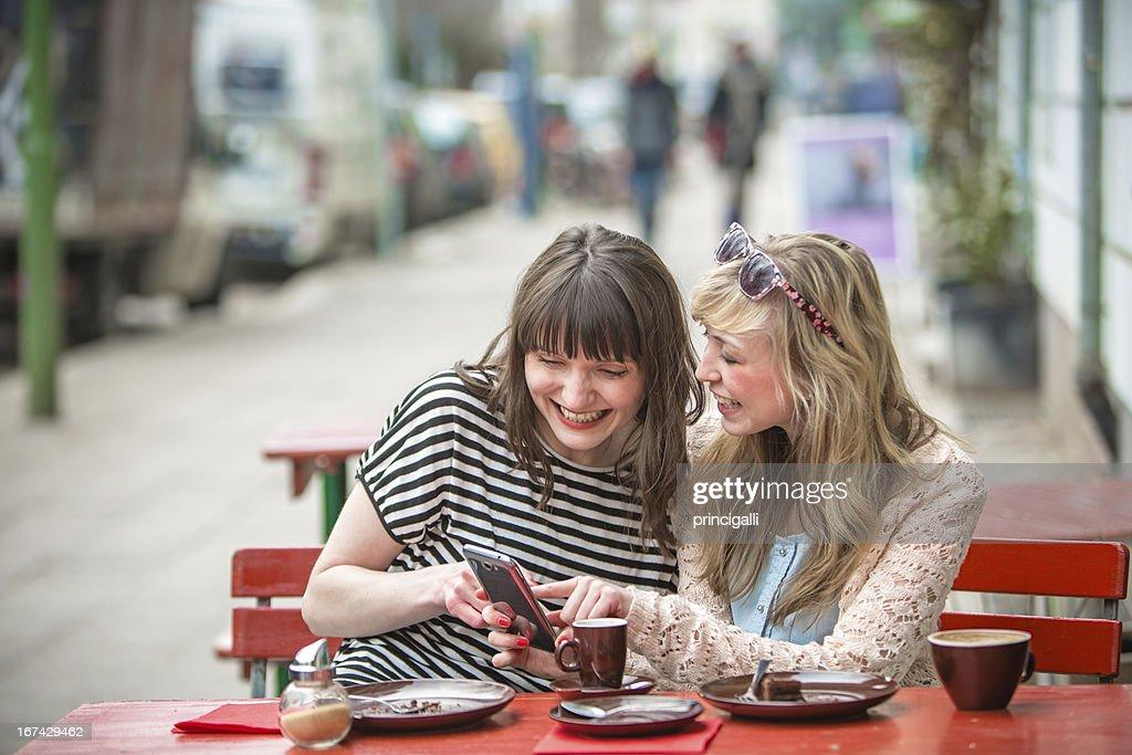 Dos mujeres con un smartphone en Café : Foto de stock