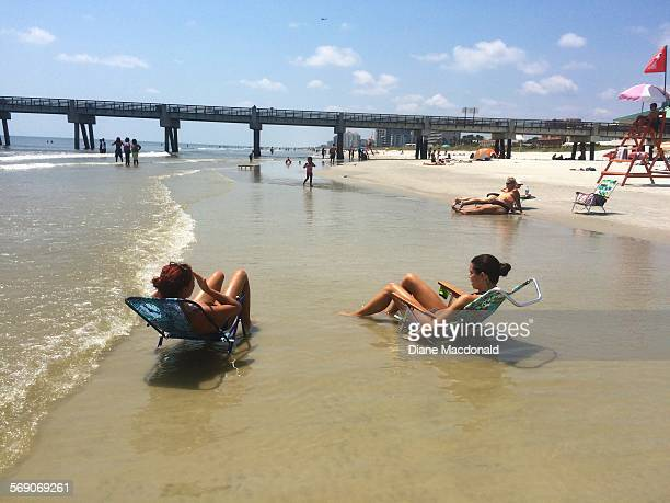 Two women in chairs in the ocean enjoying the beach at Jacksonville Beach Florida USA on July 22 2015